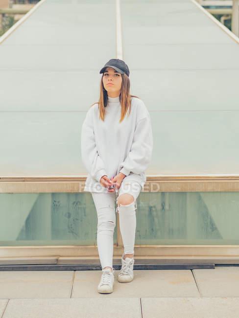 Joven hipster femenino moderno en ropa casual en el fondo de la pared geométrica mirando a la cámara - foto de stock