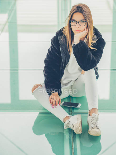 Young modern female hipster in casual clothes on background of geometric glasses looking at camera — Stock Photo