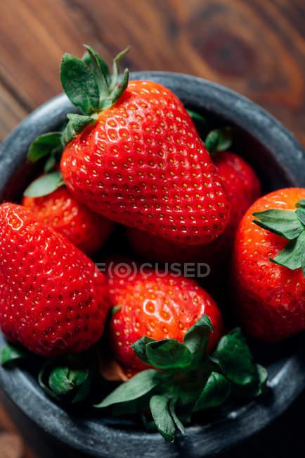 Fresas frescas maduras en un tazón de hormigón negro sobre fondo de madera - foto de stock
