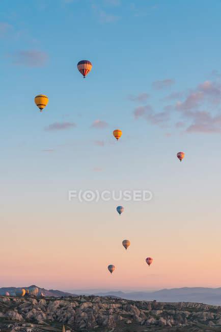 Hot air balloons flying against mountain ridge and sunny sundown sky during festival in Cappadocia — Stock Photo