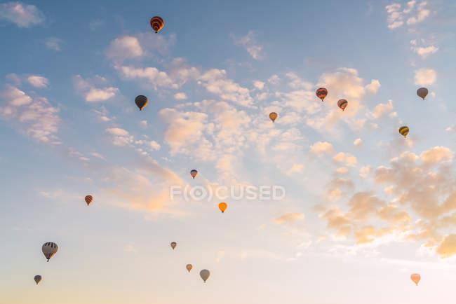 Hot air balloons flying against sunny sundown sky during festival in Cappadocia — Stock Photo