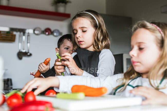 Little girls and boy cutting and peeling ripe vegetables while cooking healthy salad in kitchen together — Stock Photo