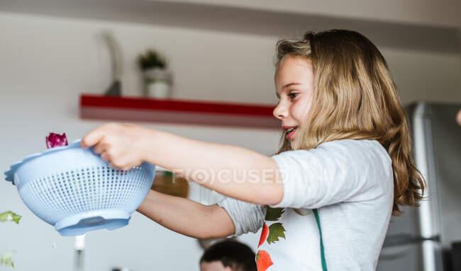 Kid washing fresh herbs in sieve under clean water while making salad in kitchen — Stock Photo