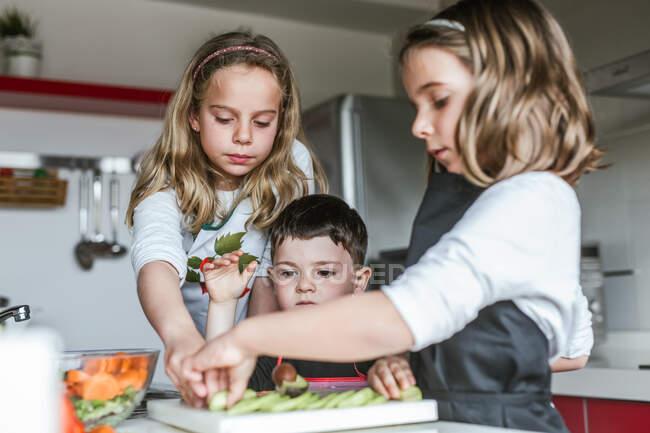 Маленькі дівчата і хлопчик зрізають і чистять стиглі овочі, готуючи здорові салати на кухні разом — стокове фото