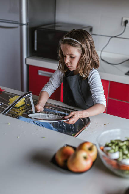 Маленька дівчинка миє тарілку над раковиною на кухні. — стокове фото