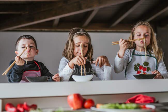 Menino e duas meninas comendo macarrão saboroso com costeletas vegetarianas e legumes enquanto se sentam à mesa em casa — Fotografia de Stock