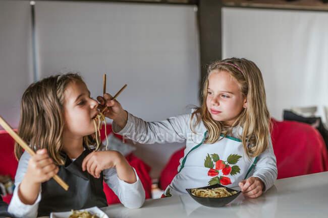 Ragazzo e due ragazze che mangiano gustosi spaghetti con costolette vegetariane e verdure mentre sono seduti a tavola a casa — Foto stock