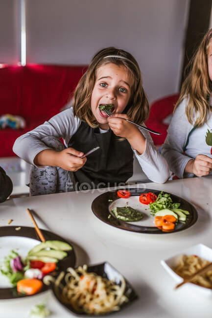 Девушка ест вегетарианские котлеты и овощи, сидя за столом дома — стоковое фото