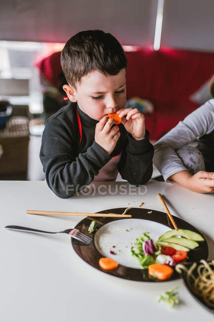 Boy eating vegetarian cutlets and vegetables while sitting at table at home — Stock Photo