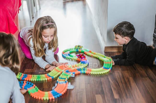 Ragazzo e due ragazze che giocano con auto e strada giocattolo sul pavimento in parquet a casa insieme — Foto stock
