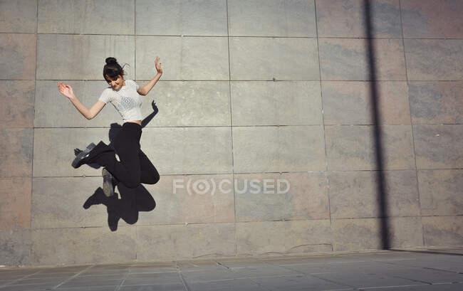 Девушка счастливо прыгает по улицам своего города — стоковое фото
