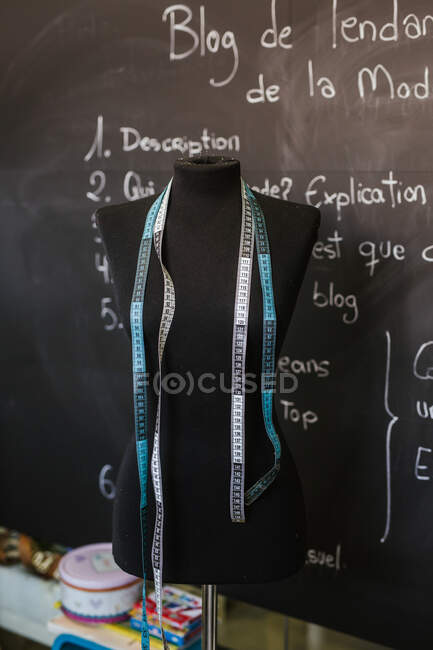 Mannequin and measuring tapes in cozy workshop — Stock Photo