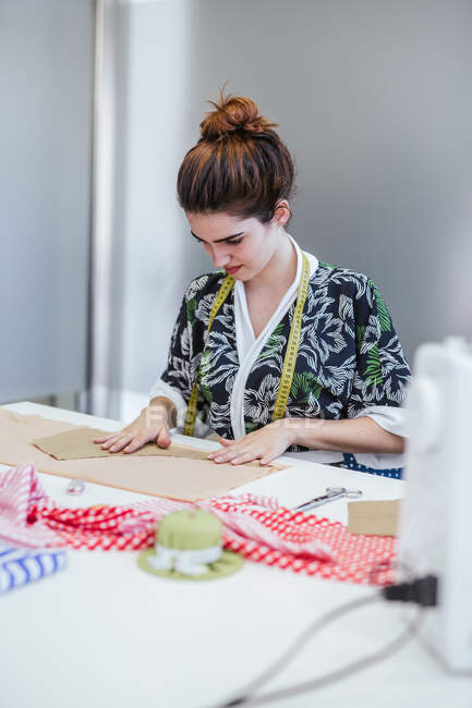 Teenage girl student practicing sewing on modern machine in cozy workshop — Stock Photo