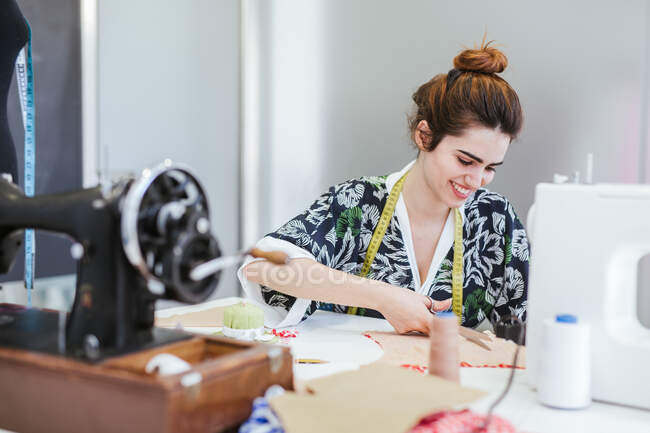 Étudiante adolescente pratiquant la couture sur une machine moderne dans un atelier confortable — Photo de stock