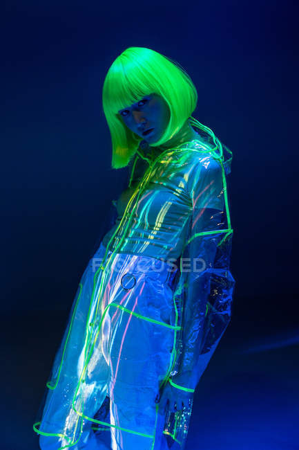 Young asian woman in yellow wig and transparent plastic wear posing in fluorescent light — Stock Photo
