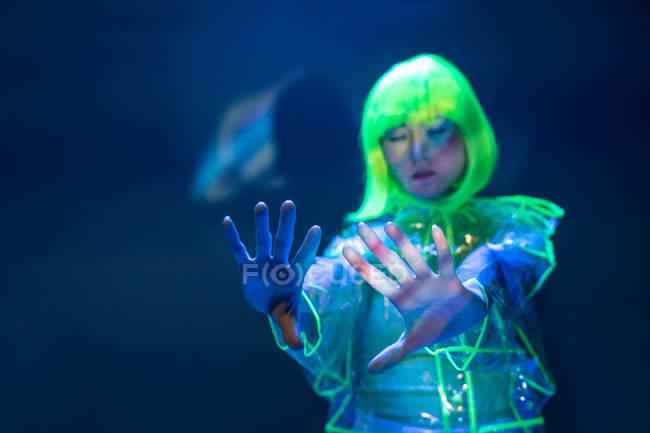 Mujer asiática joven en peluca amarilla y desgaste plástico transparente posando en luz fluorescente con las manos levantadas - foto de stock