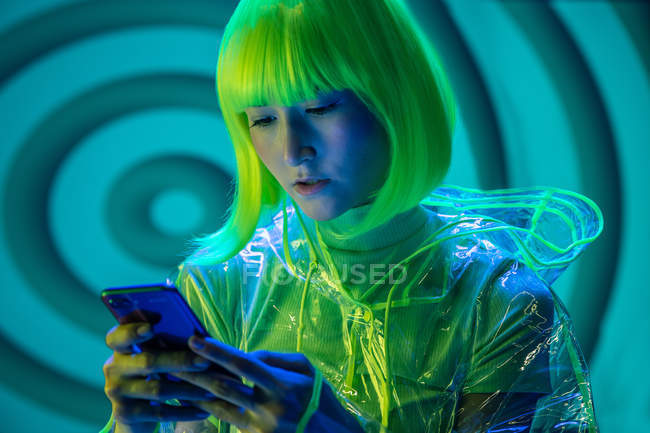 Joven mujer asiática en desgaste futurista y peluca verde usando smartphone en luz fluorescente - foto de stock