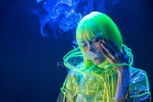 Joven bastante inusual mujer asiática en plástico impermeable transparente y pelo amarillo fumar en luz fluorescente - foto de stock