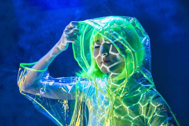 Jovem mulher asiática em peruca amarela e plástico transparente desgaste posando em luz fluorescente — Fotografia de Stock