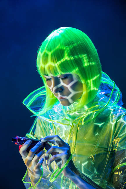 Joven bonita mujer asiática freak en impermeable de plástico transparente y peluca amarilla mirando la pluma de vapor en luz fluorescente - foto de stock