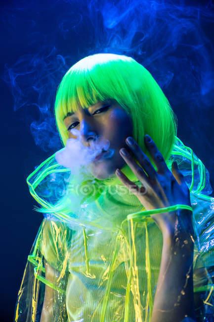 Молодая довольно необычная азиатская женщина в пластиковом прозрачном плаще и курении желтых волос при флуоресцентном свете — стоковое фото