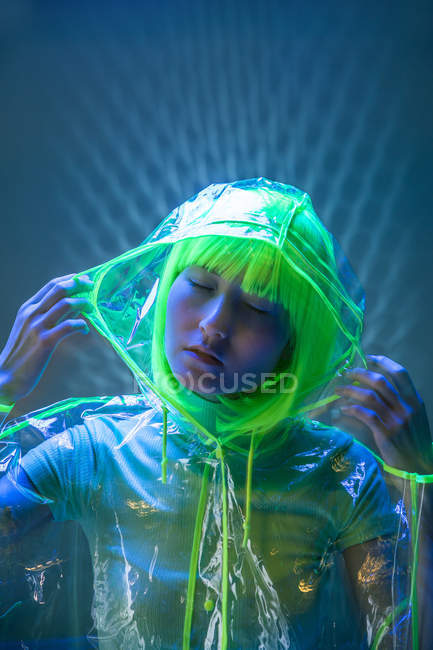 Joven mujer asiática en peluca amarilla y desgaste plástico transparente posando en luz fluorescente - foto de stock