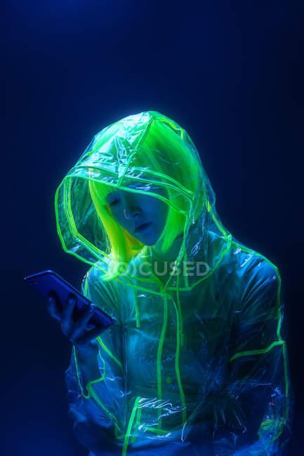 Молода Азіатська жінка в футуристичної зносу і зелений перуку за допомогою смартфона в флуоресцентного світла — стокове фото