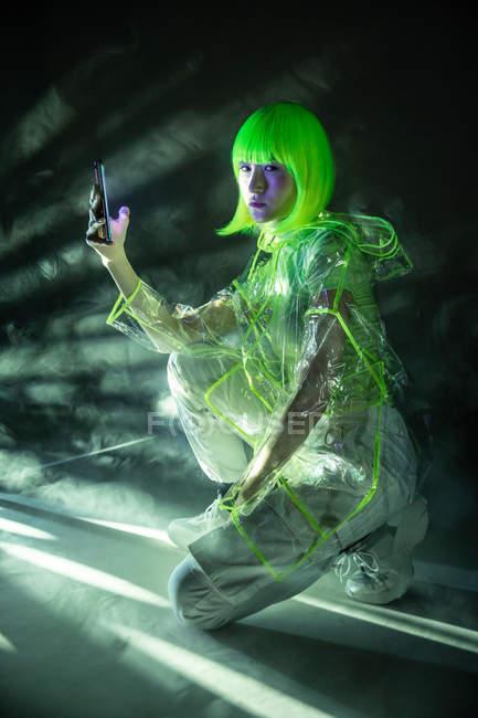 Jovem mulher asiática em desgaste futurista e peruca verde usando smartphone em luz fluorescente — Fotografia de Stock