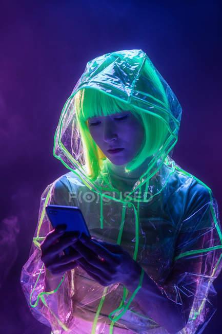 Молодая азиатка в футуристической одежде и зеленом парике с помощью смартфона в флуоресцентном свете — стоковое фото