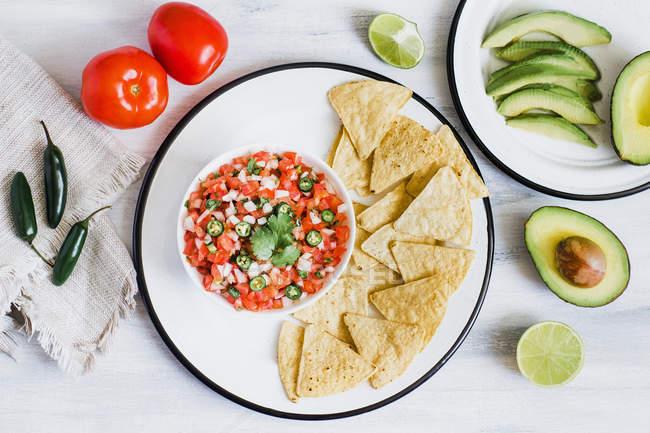 Mexikanische Gemüsesnack in Schüssel mit Chips auf weißem Holztisch serviert — Stockfoto