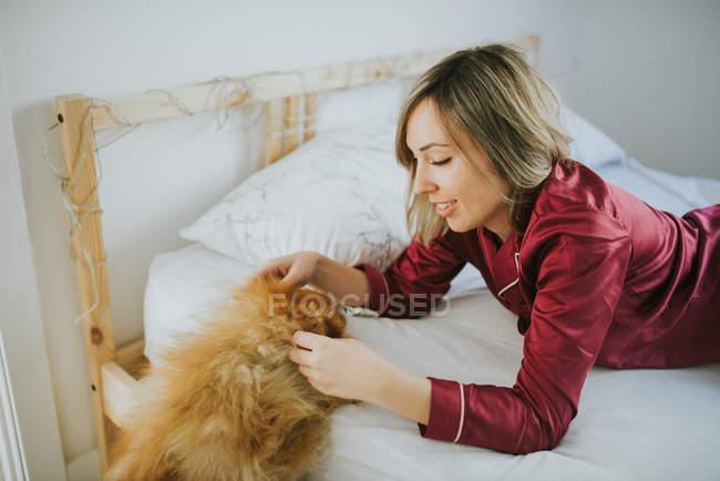 Молодая счастливая улыбающаяся привлекательная женщина в пижаме лежит в постели с маленькой пушистой собачкой — стоковое фото