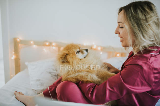 Young happy smiling attractive woman in pajamas sitting in bed with little fluffy dog — Stock Photo