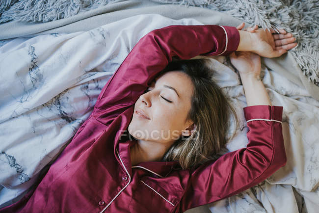 Young pretty woman in pajamas smiling while relaxing on bed — Stock Photo