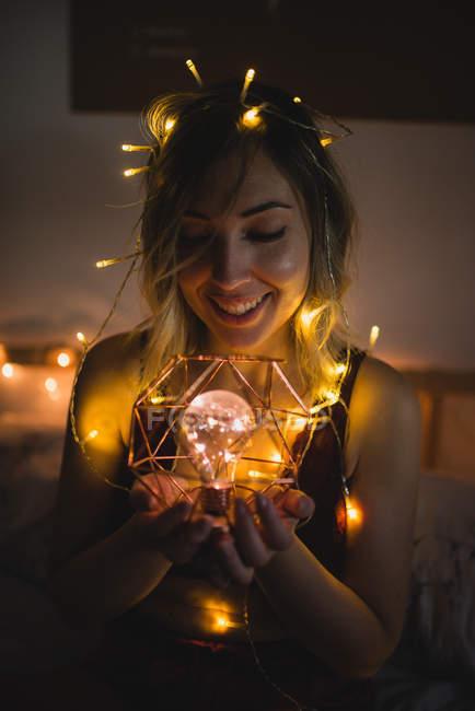 Jeune femme en sous-vêtements assis dans le lit entouré de guirlande de lumière et tenant ampoule — Photo de stock