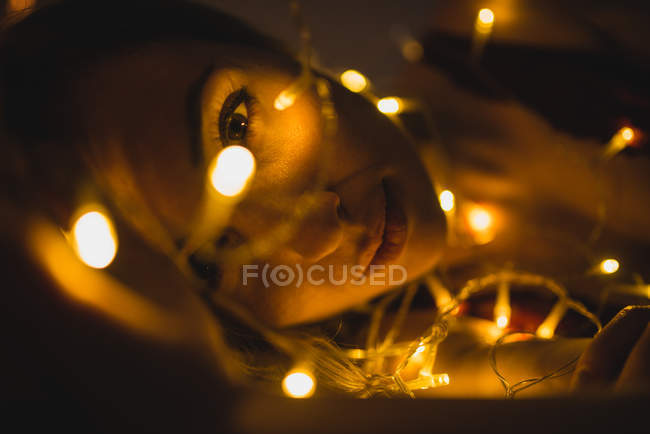 Крупным планом молодая женщина, лежащая в окружении легкой гирлянды — стоковое фото