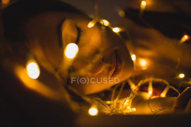 Close-up of young woman lying surrounded by light garland — стоковое фото