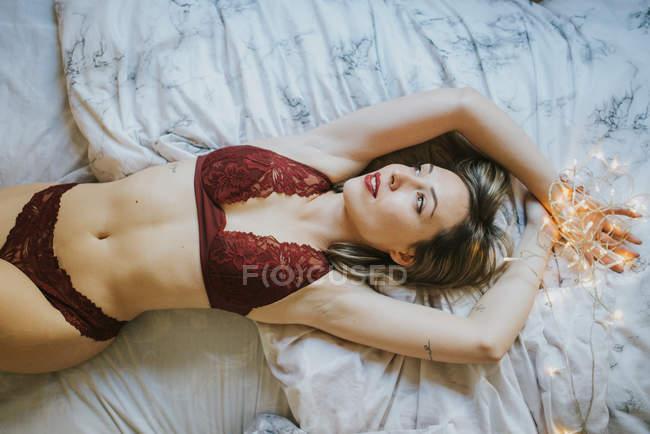 Jovem mulher sedutora em roupa interior deitada na cama de manhã — Fotografia de Stock