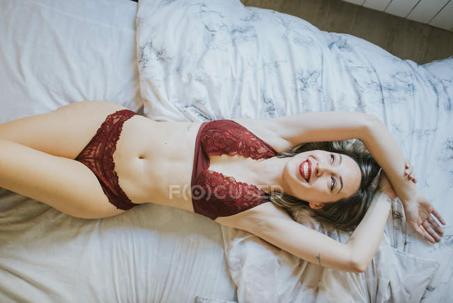 Young seductive woman in underwear lying in bed in morning — Stock Photo