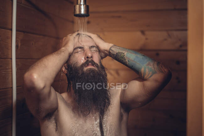 Middle aged bearded man with tattoo taking shower in wooden bathroom — Stock Photo