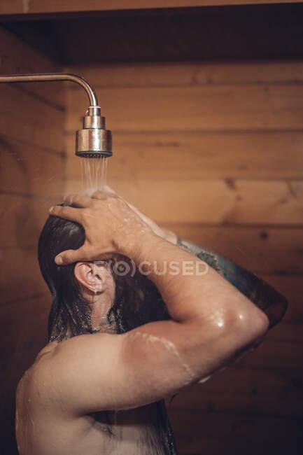 Man taking shower in wooden bathroom — Stock Photo