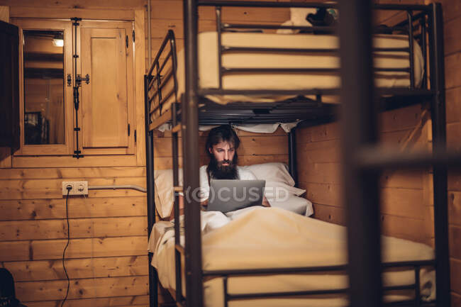 Man using laptop in rustic bunk bed — Stock Photo