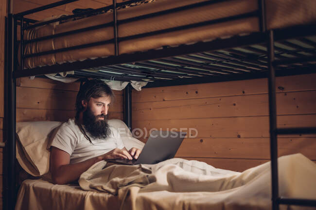 Concentrated bearded hipster working on laptop while lying in simple bunk bed of country wooden house — Stock Photo