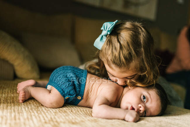 Cute little girl kissing innocent newborn baby in back lying on sofa at home — Stock Photo