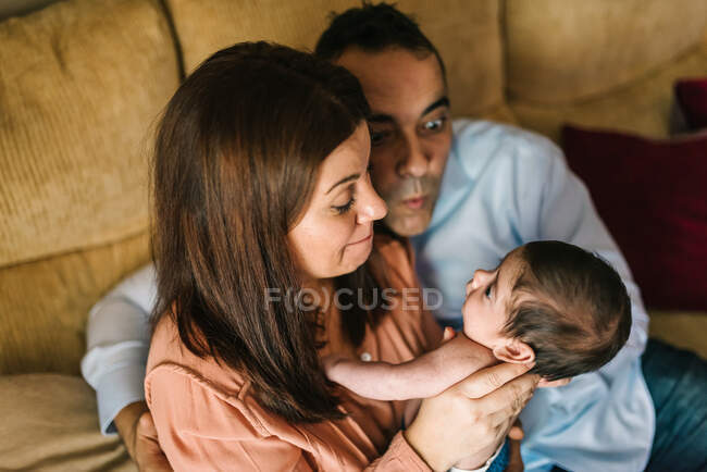 Happy young mother holding newborn baby wrapped in blanket and father sitting on sofa next to them at home — Stock Photo