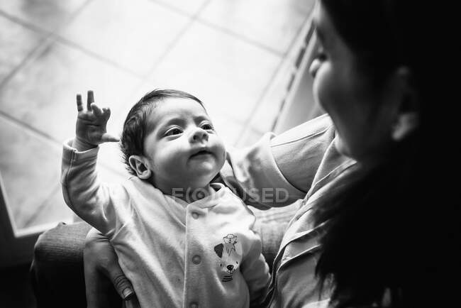 Back view unrecognizable brunette mom hugging cute little baby looking away at home — Stock Photo
