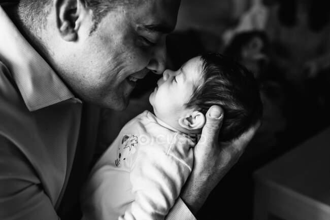 Отец обнимает милую малышку, смотрит вдаль на дом. — стоковое фото