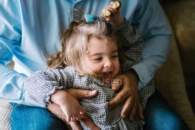 Father hugging cute little girl looking away and having fun at home — Stock Photo