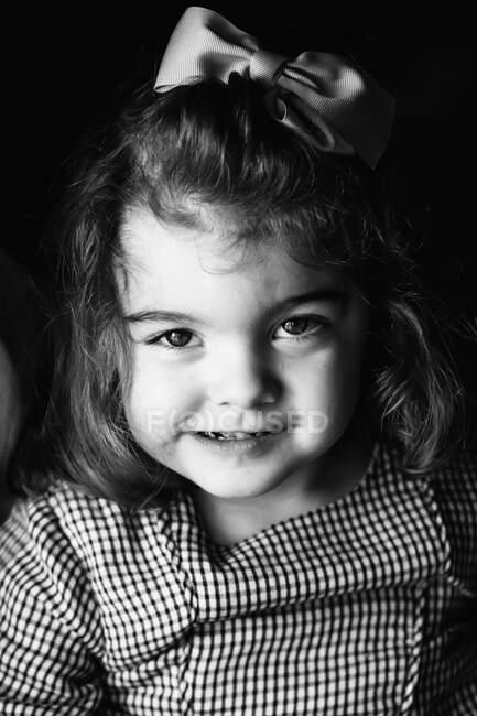Piccola bella ragazza guardando la fotocamera su uno sfondo scuro — Foto stock