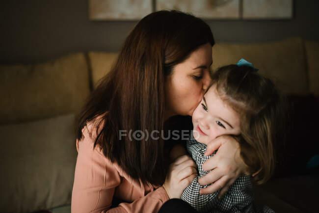 Morena mamá abrazando lindo poco hija mirando lejos en casa - foto de stock