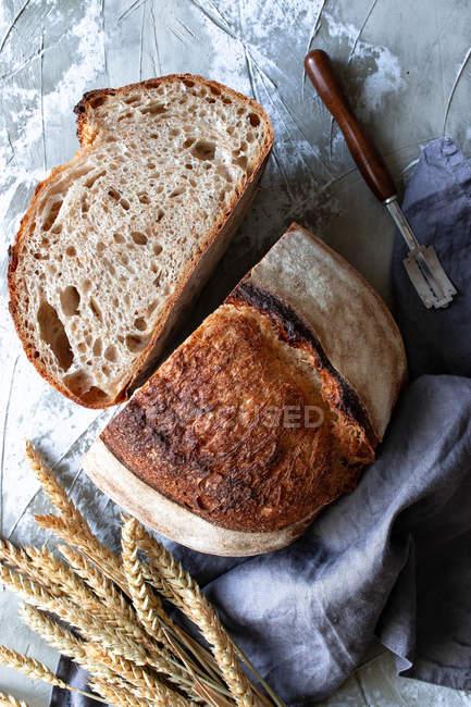 De arriba pan de masa fermentada fresco casero en mantel sobre mesa de madera - foto de stock